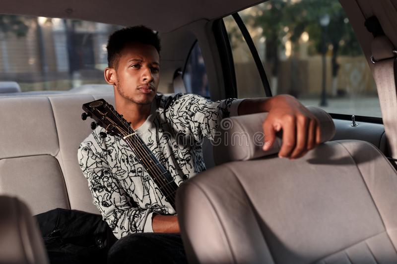 Frowning man in car holding a guitar, seated in back seat of car, put his hand on the driver`s seat. light on his face. stock image