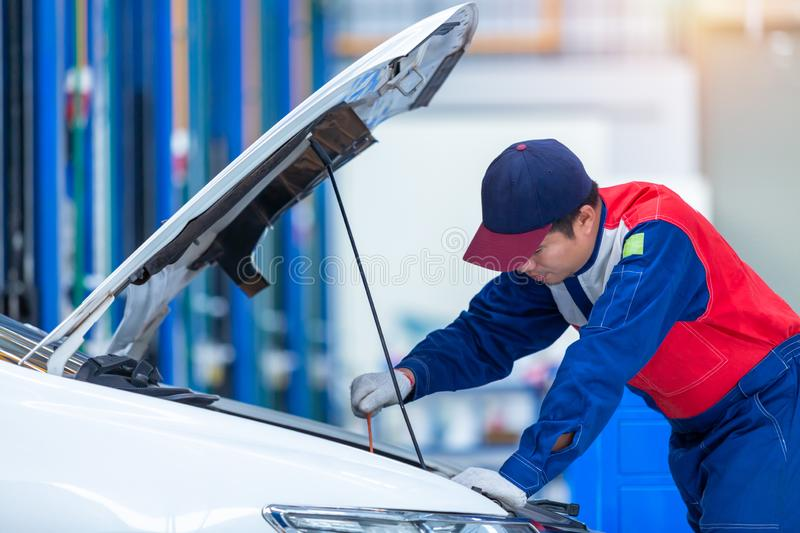 Young man car mechanic in a car repair service center is analyzing engine problems and checking the engine. Auto mechanic working royalty free stock photos