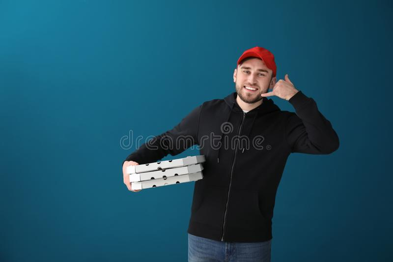 Young man with cardboard pizza boxes on color background. Food delivery service stock photo