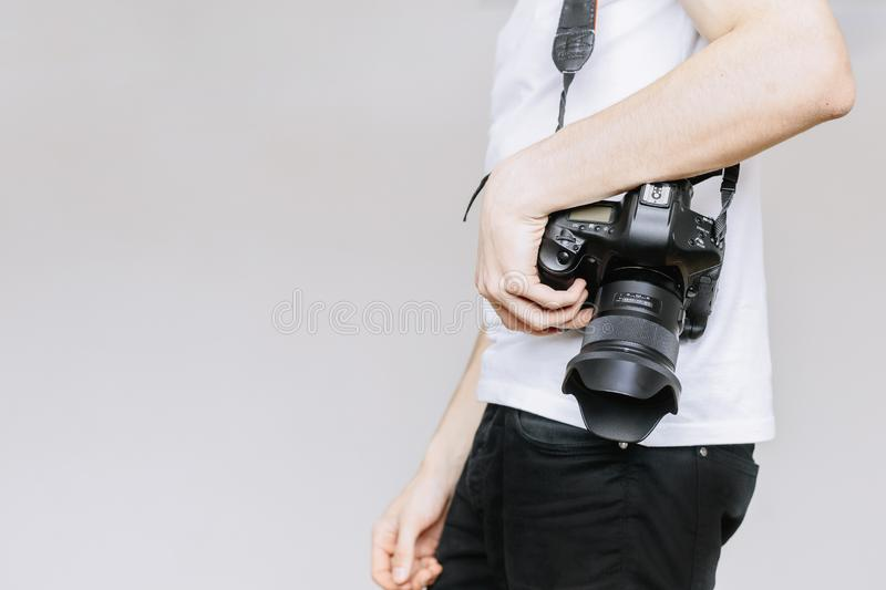 Young man carries a photo camera on his shoulder. Isolated gray background stock photography