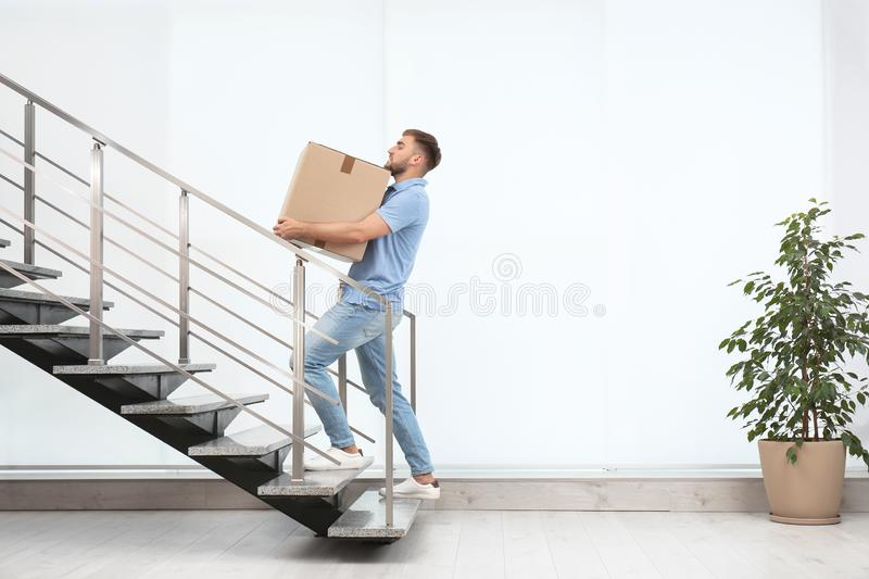 Young man carrying carton box upstairs indoors stock photos