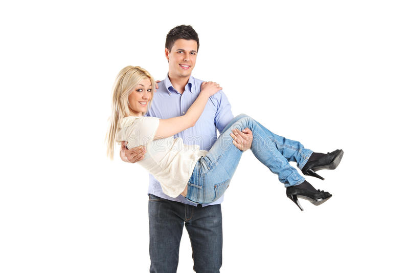 Young man carrying his girlfriend royalty free stock image
