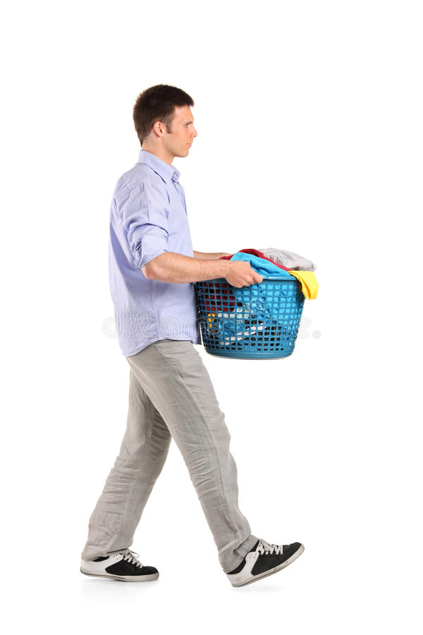 Young man carrying a laundry basket royalty free stock photos