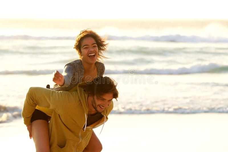 Young man carrying smiling woman on back at the beach royalty free stock images