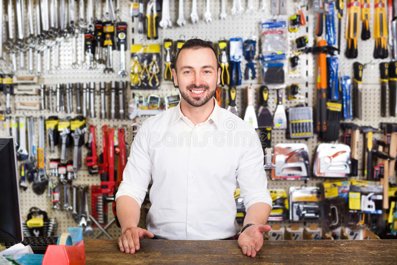 Young man cashier at pay desk. Smiling young man cashier standing at pay desk in household store royalty free stock image