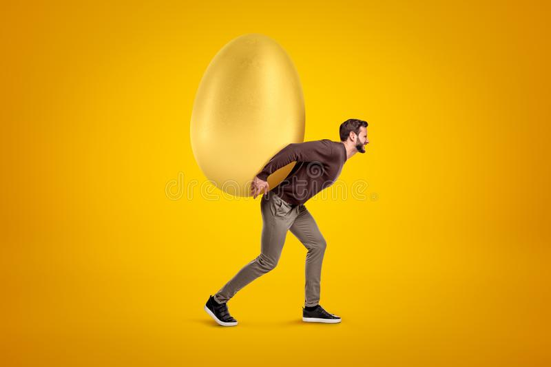 Young man in casual clothes carrying big golden egg on his back on yellow background royalty free stock images