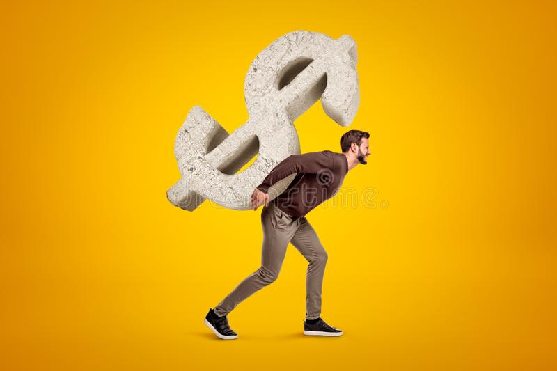 Young man in casual clothes carrying big stone dollar sign on his back on yellow background royalty free stock images