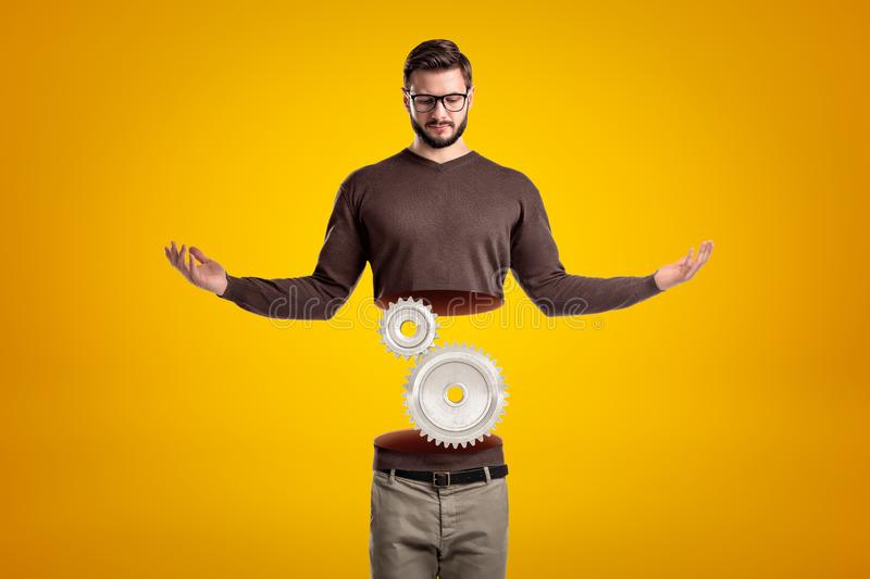 Young man in casual clothes cut in half with silver gear wheels inside on yellow background stock photos