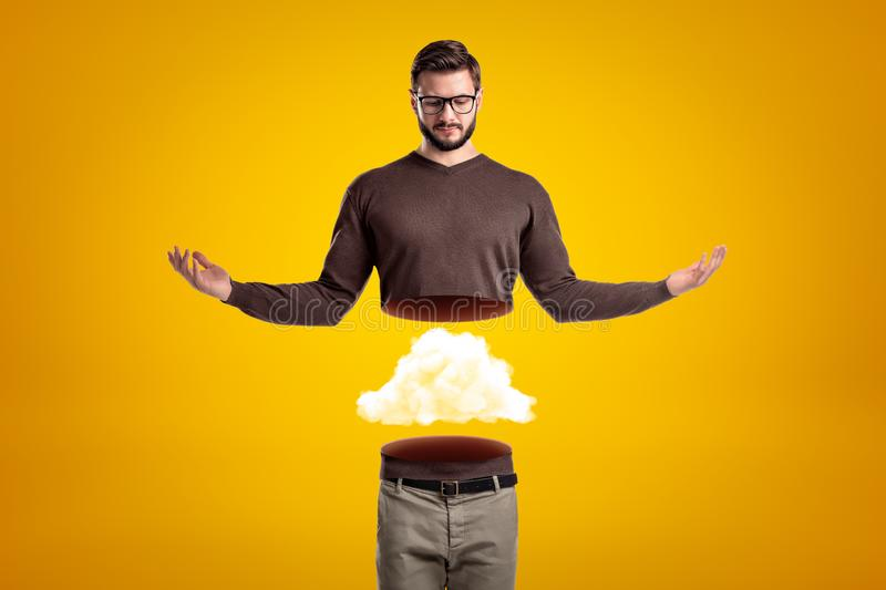 Young man in casual clothes cut in half with white cloud inside on yellow background royalty free stock images