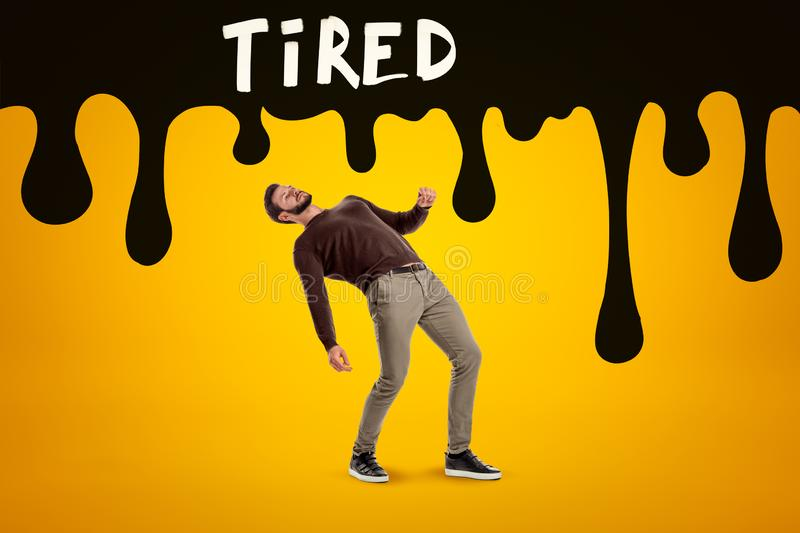 Young man in casual clothes falling with black TIRED sign above on yellow background stock images