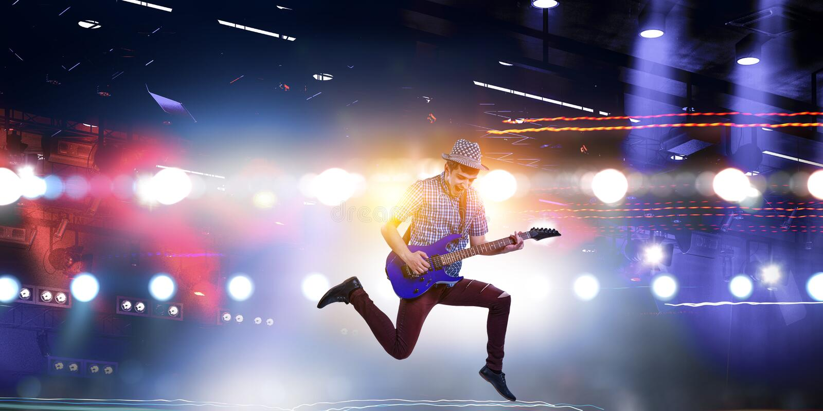 Guitar player jumping with guitar while playing royalty free stock images