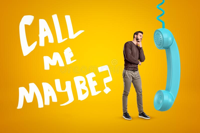 Young man in casual clothes standing in half-turn, one hand on chin, near big cyan phone receiver on yellow background royalty free stock image