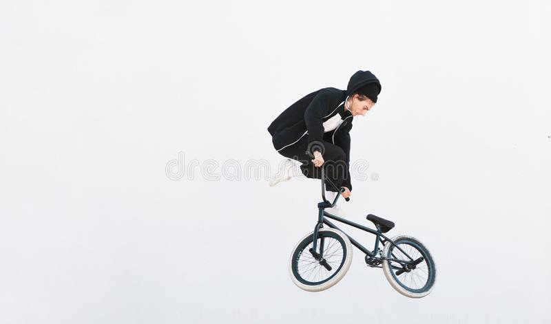 Young man in casual clothing makes a trick on a bmx bike, isolated on a white background royalty free stock photo