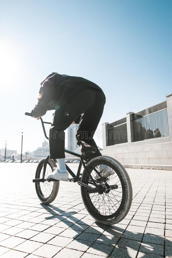 Young man in casual clothing rides a bmx on a sunny summer day. Bmx rider`s back stock photos