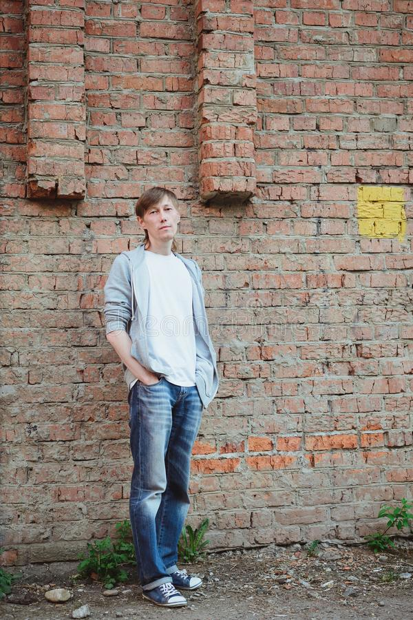 Young man  in casual clothing standing in full size near brick wall background. Young 30s age man  in white and blue casual clothing standing with his hands in royalty free stock images