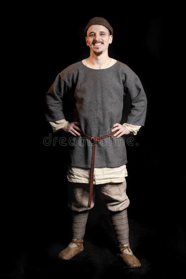 Young man in casual gray clothes and a hat of the Viking Age early Middle Ages smiles. His hands on hips stock photography