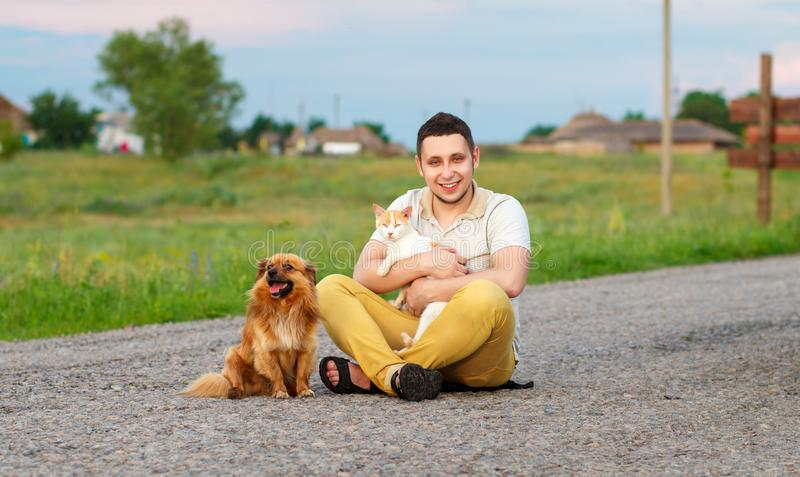 A young man with a cat and a dog are sitting on the road, the guy in the yellow jeans holding a cat in her arms, a dog sitting on stock photo