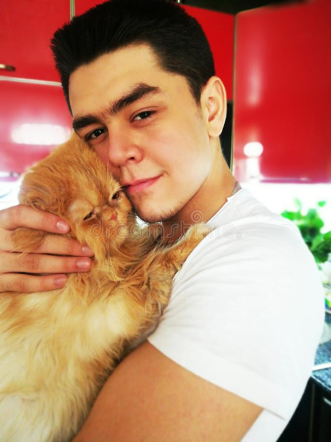Cat with Young Man. Orange Persian Cat. Happiness. Lover Man, Hugging and Cuddling his Happy Domestic Cat Pet. Love to the animals. Young man with cat. Orange stock photo