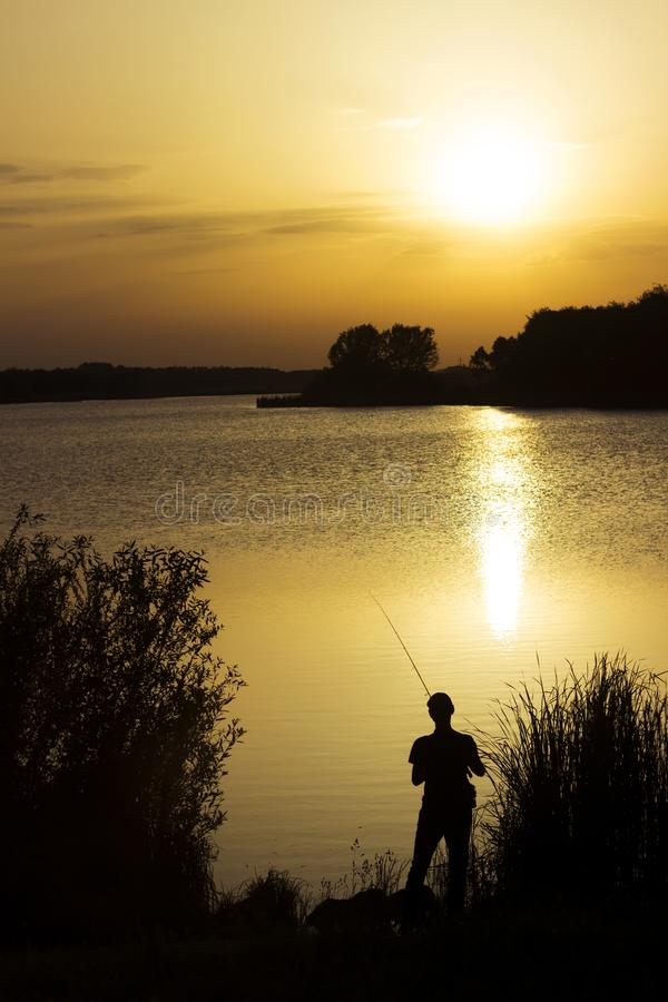 A young man catches fish in the lake at sunset. Beautiful sun reflection on the water. Relaxation stock photos