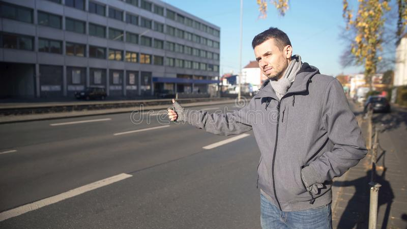 Young man catching automobile in unknown city, cheap traveling, hitchhiking royalty free stock photography