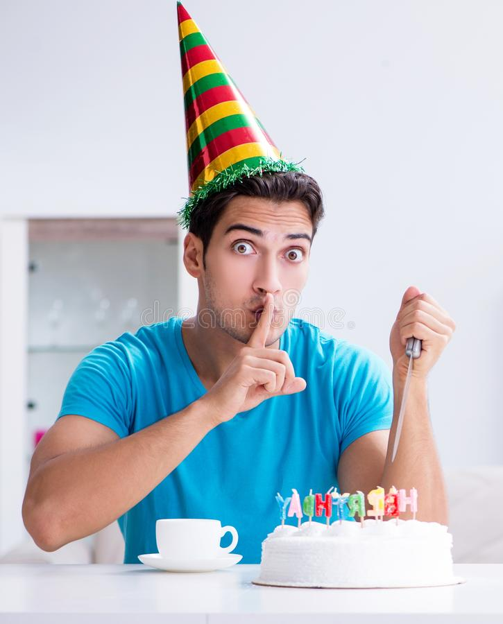 Young man celebrating birthday alone at home. The young man celebrating birthday alone at home royalty free stock images