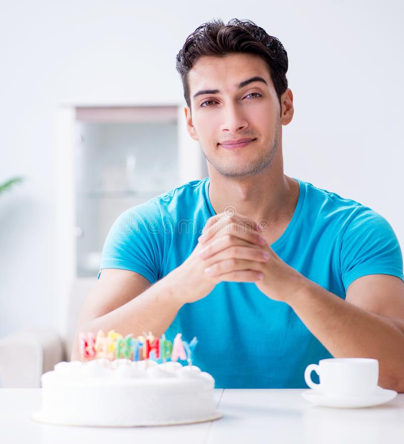 Young man celebrating birthday alone at home. The young man celebrating birthday alone at home stock photo
