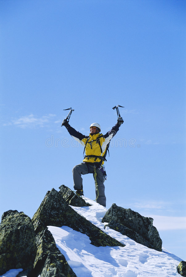 Young man celebrating reaching the top of mountain royalty free stock photos