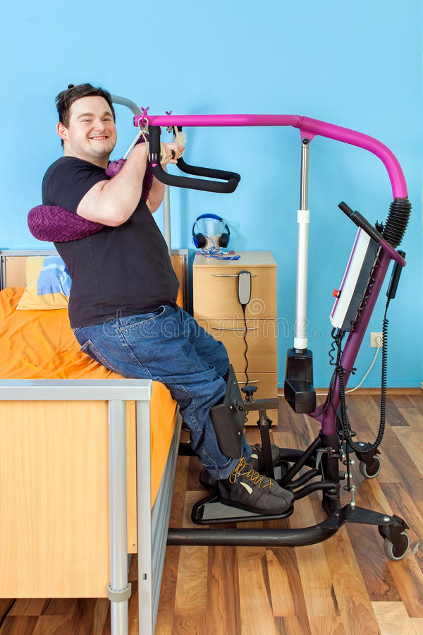 Young man with cerebral palsy using a patient lift. Spastic young man with infantile cerebral palsy from birth complications using a patient lift to transfer stock images