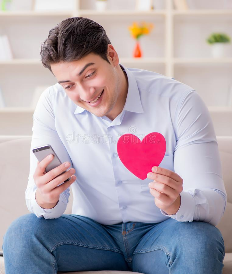Young man chatting with his sweetheart over mobile phone stock photography