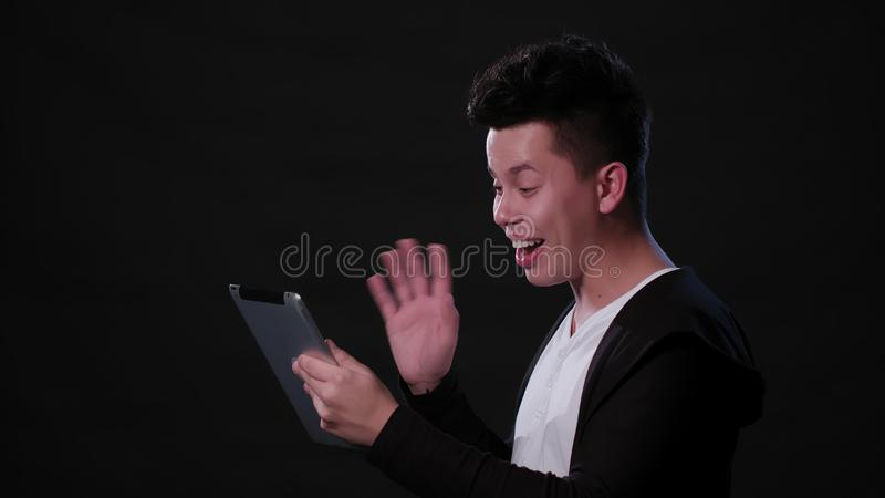 Man Chatting Online Against a Black Background royalty free stock image