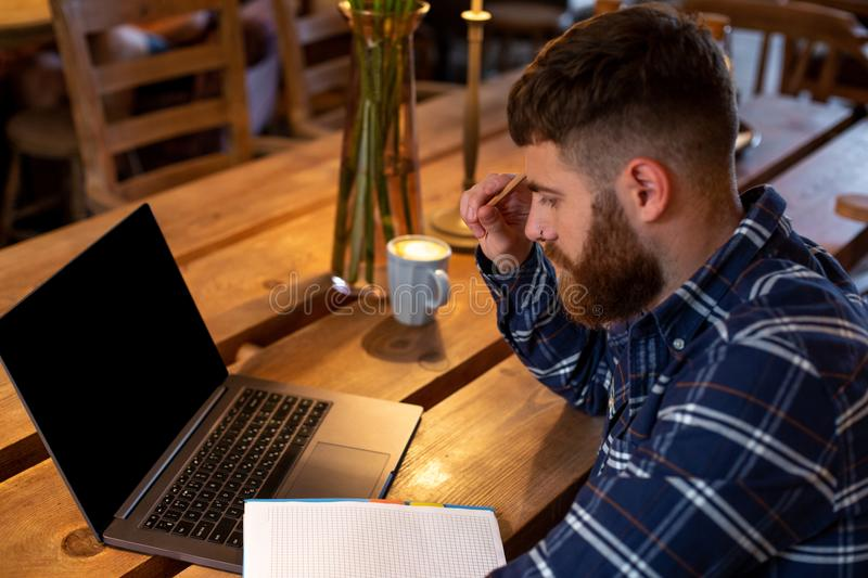 Young man chatting via net-book during work break in coffee shop, male sitting in front open laptop computer with blank stock photo