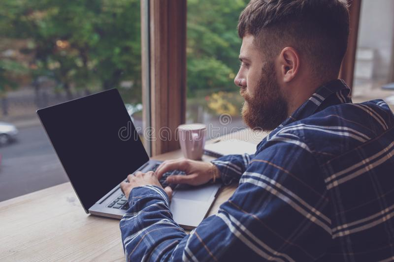 Young man chatting via net-book during work break in coffee shop stock photo
