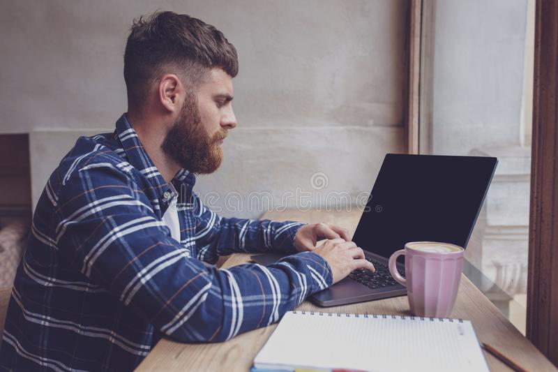 Young man chatting via net-book during work break in coffee shop royalty free stock images