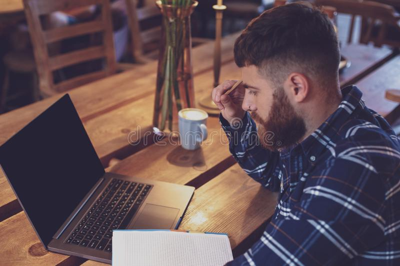 Young man chatting via net-book during work break in coffee shop stock images