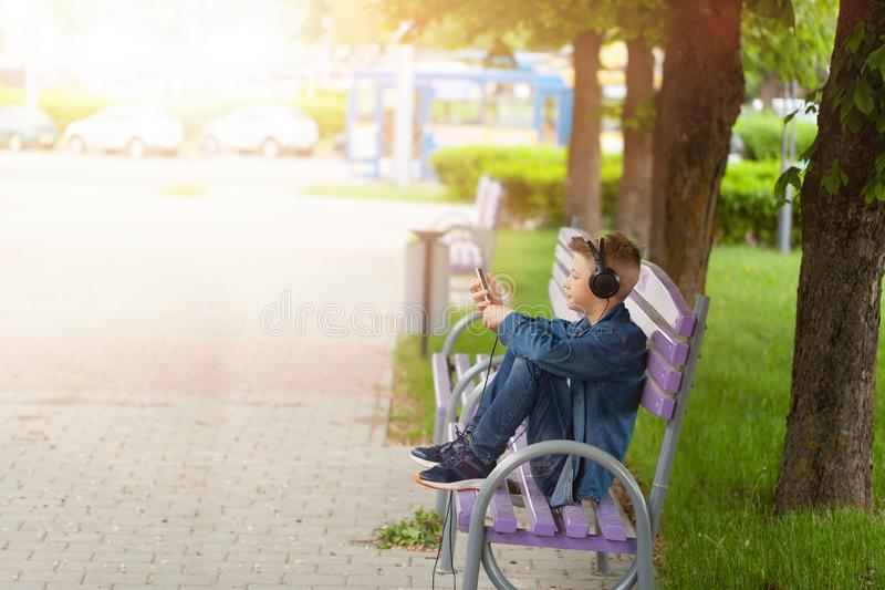 Young man checking his mobile phone outdoors. Teenager in headphones uses his smartphone royalty free stock photography