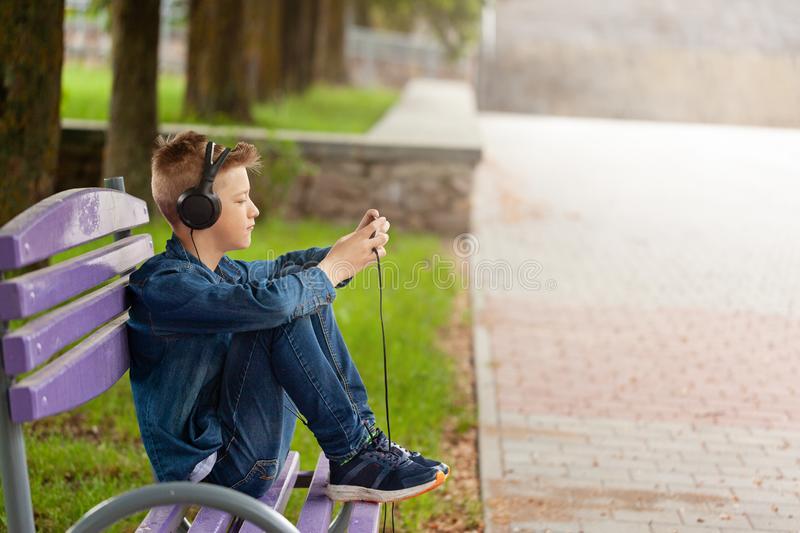 Young man checking his mobile phone outdoors. Teenager in headphones uses his smartphone stock images
