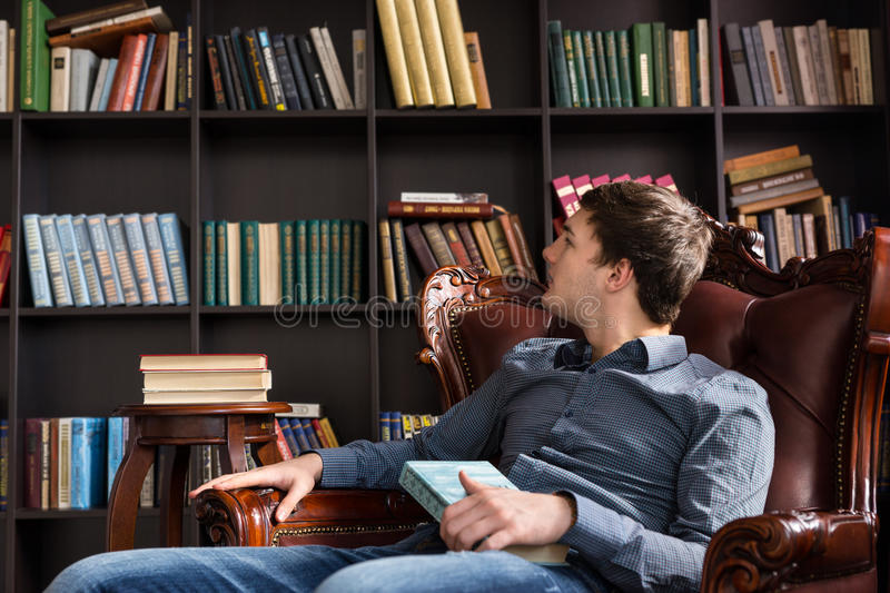 Young man checking out books in a library. Sitting in a comfortable armchair reading the titles of books on the shelves royalty free stock photos