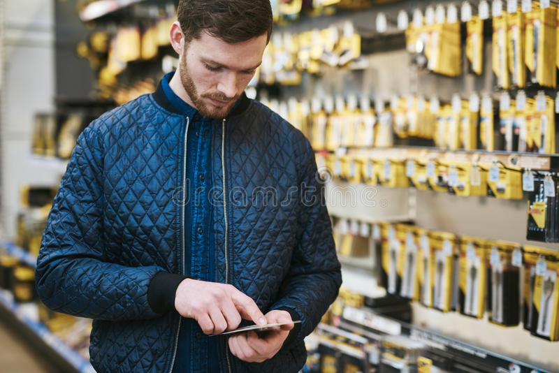 Young man checking a text message in a store royalty free stock photography