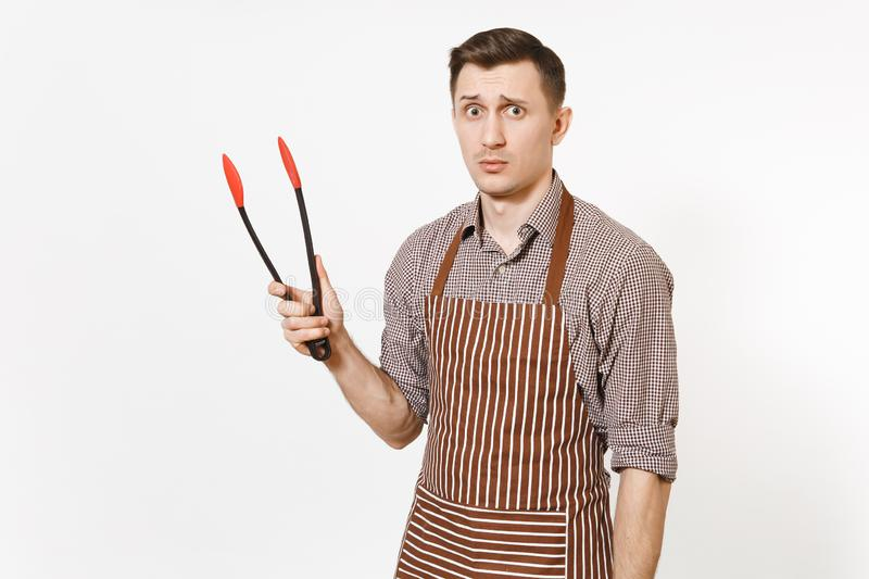 Young man chef in striped brown apron, shirt holding black kitchen serving plastic pair of tongs for salad isolated on stock images