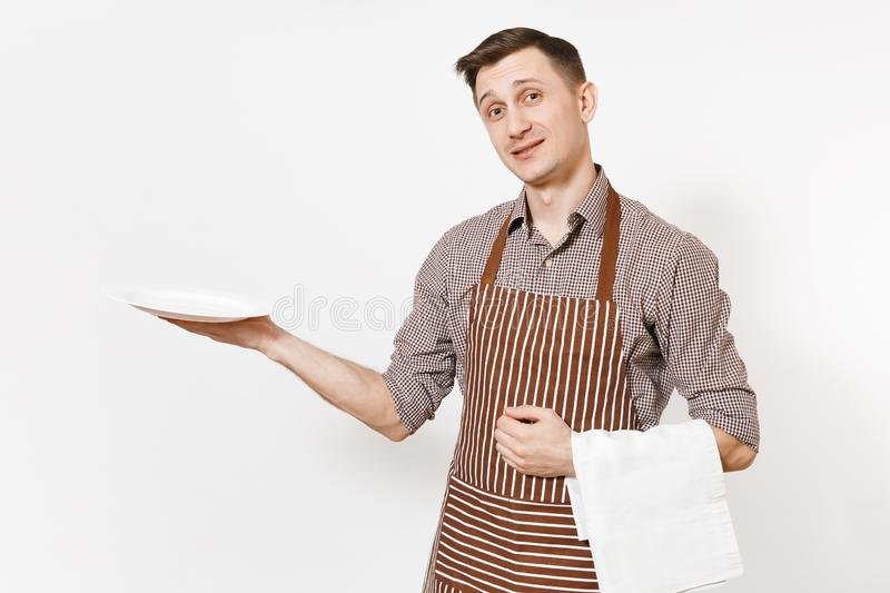Young man chef or waiter in striped brown apron, shirt holding white round empty clear plate, towel napkin isolated on royalty free stock image