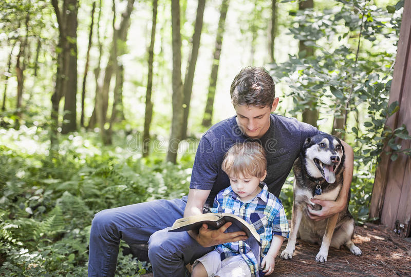 Young man and child reading royalty free stock photo