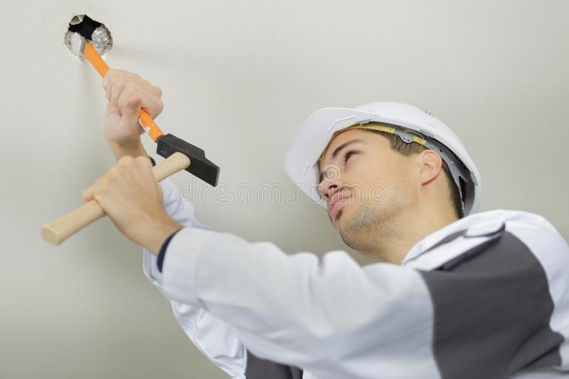 Young man with chisel and hammer. Young man with a chisel and hammer royalty free stock images