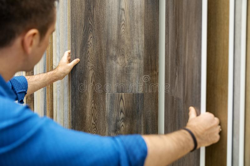 Man choosing floor laminate for his home in flooring shop stock photo