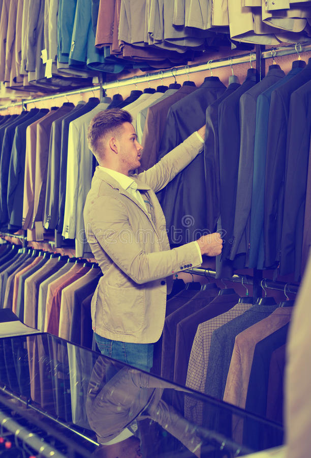 Download Young Man Choosing New Suit In Men's Cloths Store Stock Photo - Image of indoors, fabric: 83701648