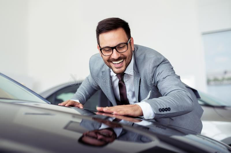 Young man is choosing a new vehicle in car dealership royalty free stock image