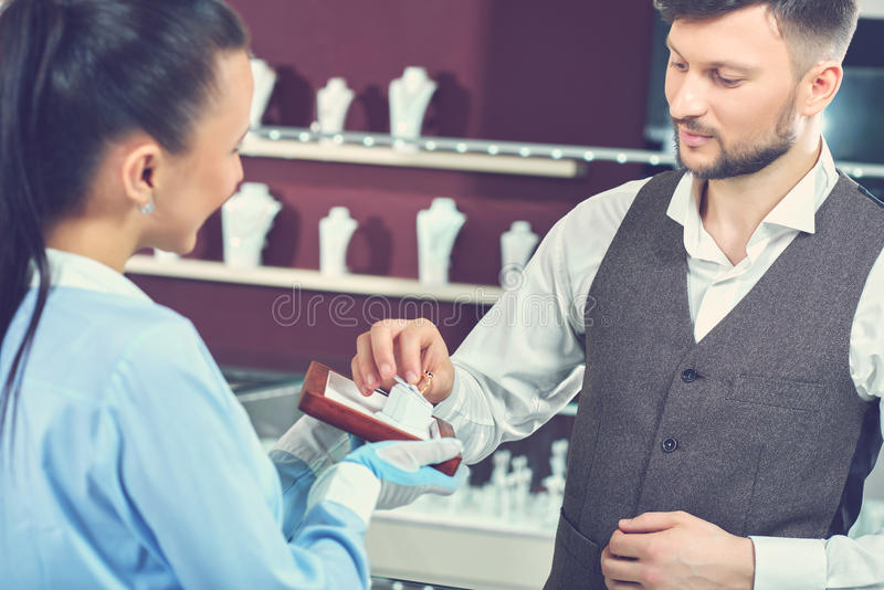 Young man choosing present at jewelry store. royalty free stock image