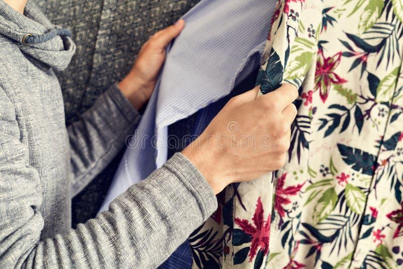 Young man choosing a shirt royalty free stock image