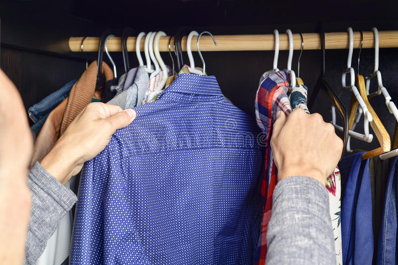 Young man choosing a shirt from a clothes rack stock photo