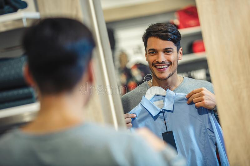 Young man choosing shirt and looking to mirror in store stock image