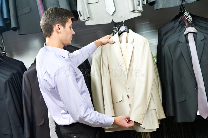 Young man choosing suit in clothes store stock photography